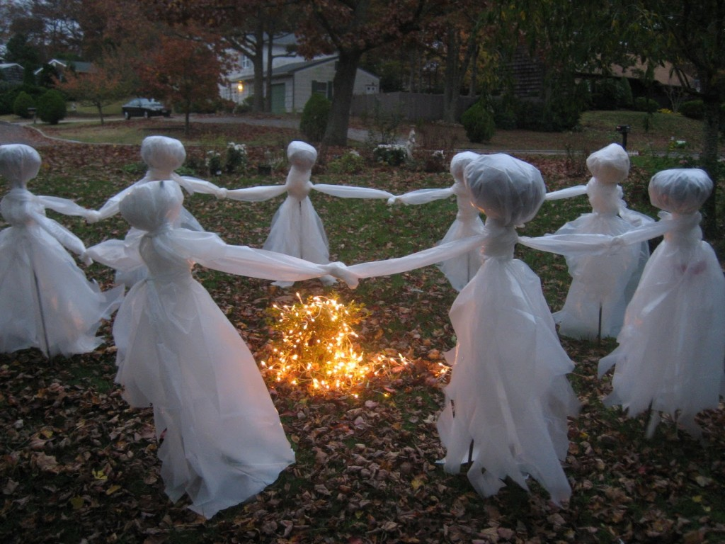 this outdoor decor idea brings a group of ghosts dressed in white to your yard all holding each - Halloween Yard Decoration Ideas