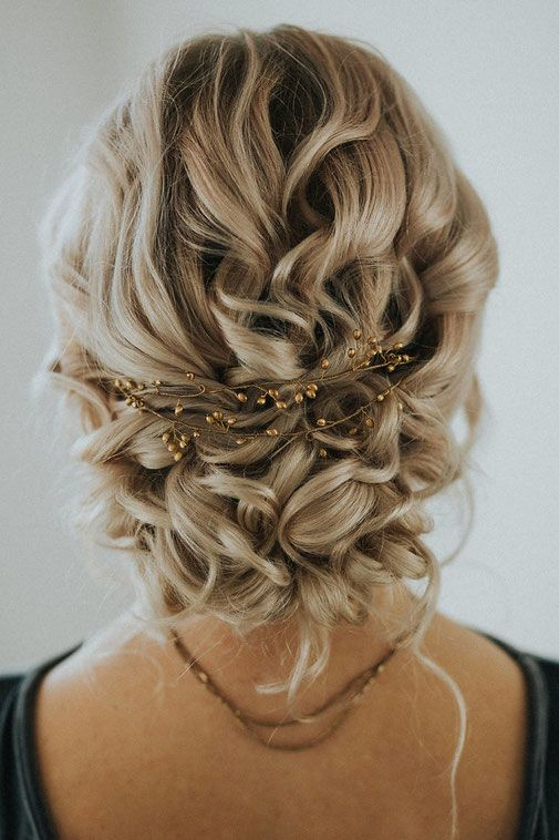 Low Bun with Curly Strands and Golden Embellishment